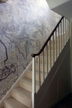 When trying to create a unique and stylish hallway for your home, think about finding a special wallpaper that perhaps you wouldn't usually put in your living room - this map wallpaper in neutral grey tones works perfectly against a white ballustrade.