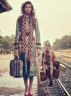 Posing with a bag of luggage, Ondria models a colorful trench from Gucci by Alessandro Michele with checkered scarf
