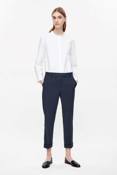 A straight tailored fit with neat press folds along the front and cuffed hems, these trousers are made from crisp technical fabric with a textured feel.…