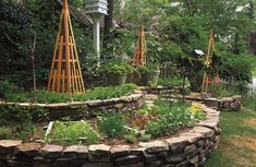 Nicely graded flat stones make formal terraces in Sharon Abroms garden in Atlanta. The rockwork terraces elevate the lettuces, basil, peppers, and mustard greens and provide a platform for the pyramidal wooden tomato cages. The design is as much landscape art as it is practical vegetable garden.