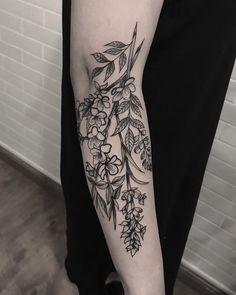 Tatuagem criada por Ricardo Garcia de Londrina. Ramo, com folhas e flores em blackwork no braço.