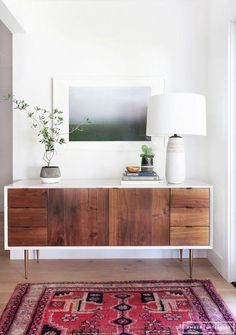 Gorgeous midcentury modern entryway with a walnut wood and white copper peg leg credenza, ceramic table lamp, modern fine art photography framed print and vintage red Persian area rug.