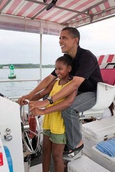 """President Barack Obama and daughter Sasha steer the """"Bay Point Lady"""" during a tour of St. Andrews Bay off Panama City Beach, Fla., Aug. 15, 2010"""