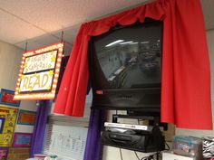 Red curtains around TV and sign in the reading corner.