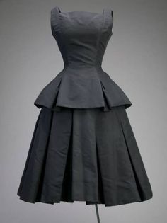 """Cocktail dress, Christian Dior for Christian Dior, Inc., Paris, France: ca.1954, silk faille. """"A fine piece of twine and a metal """"seal"""" hangs from the interior side seam, which signifies that import tax was paid on this garment. Without the removal of the original lining, this seal would not be visible. This is the only dress in the museum's Dior collection that still contains the import tax seal."""""""