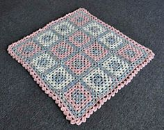 This cozy blanket is squishy soft, and works up quickly in Cuddles. It is made up of 16 traditional granny squares with border.