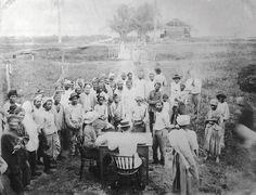 Javaanse en Hindoestaanse arbeiders wachten op de uitbetaling van hun loon op de Clevia plantage 1903. Stichting Surinaams Museum, Paramaribo
