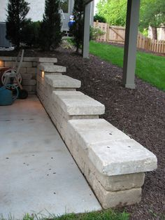 This retaining wall steps down a slope and keeps debris from washing onto the patio under a tall deck. Soil is graded away from the foundation of the house to keep excess water out of the basement. Note the wall light to illuminate this area at night. A hot tub sits just to the left side, out of the picture.