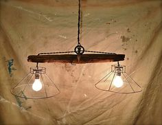 Rustic hanging light fixture made from and old plowing yoke. The upcycled weather beaten wooden