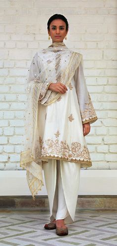 Rimple and Harpreet Narula. Ivory Chanderi silk A-line shirt featuring delicate resham embroidery; paired with a soft tulle dupatta and silk dhoti-pants