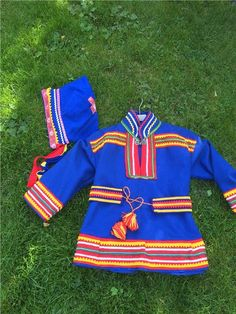 Here is a Sami costume for children. Frock with belt and hat. Blue cap. Finnish design by Noitarumpu Rovaniemi, Finland. The suit is in very condition. However, missing loop on pewter buckle. Chest width 96 cm. Length back collar 56 cm apart. Sleeve length 36 cm. 4/5