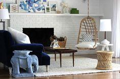blue velvet sofa, white brick fireplace, hanging chair, rattan stool. Styling by Emily Henderson.