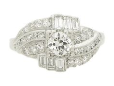 Diamond cluster ring. The central round old cut diamond is set with four squared corner claws to an open back with an approximate weight of 0.40 carats, framed above and below by two off centre horizontal rows of three rectangle baguette cut diamonds in open back rubover settings with a combined approximate weight of 0.36 carats, between twenty six round eight cut diamonds weighing approximately 0.50 carats in grain and rub over settings which form stepped and swirled shoulders. Total…
