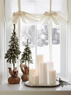 Group candles in a window for a warm holiday decoration. For more shots of this house: http://www.midwestliving.com/homes/seasonal-decorating/white-decorating/page/15/0