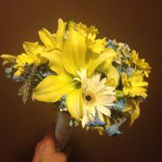 Yellow asiatic lilies, yellow daisy poms, white stock, blue delphinium, aster and limonium.