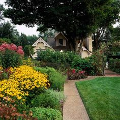 We love this small yard landscaping idea: Place bold, bright colors in front of where you'll view them. Because they catch your attention first, the rest of the small garden landscape beyond will seem to recede, helping it to feel larger.