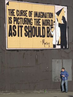 Street art : Posters pasted on a big wall by the artist Morley from Los Angeles