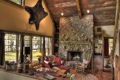 Une belle cheminée en pierre trône au milieu du séjour de cette maison de vacances rustique