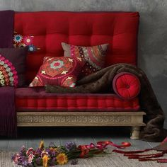 crimson sofa and embroidered pillows