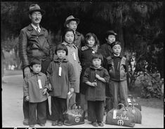 May 8, 1942 — Hayward, California. Members of the Mochida family awaiting evacuation bus. Identification tags are used to aid in keeping the family unit intact during all phases of evacuation. Mochida operated a nursery and five greenhouses on a two-acre site in Eden Township. He raised snapdragons and sweet peas. Evacuees of Japanese ancestry will be housed in War Relocation Authority centers for the duration.