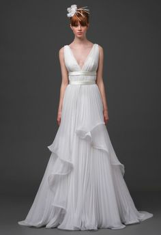 The Vega bridal gown by Alberta Ferretti Spring 2015 is a Grecian goddess dream to life! The whimsy gown has a deep V-neck with an exquisitely pleated A-line skirt that features delicate ripples at the edges of this pretty gown. By creating a modern twist to a classic silhouette this gown stands the test of time. #wedding #bride #weddingdress