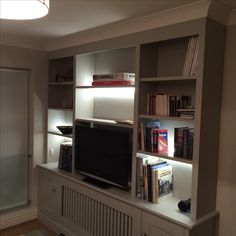 Purpose built bookcase incorporating a radiator cover providing stylish storage for a small room