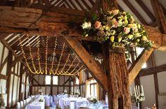 A big single swag fairy light canopy at the Loseley Barn #wedding