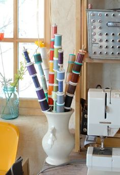 Need to keep track of a handful of special threads for your most current project? Why not organize thread spools on dowel rods and put them in a vase right next to your sewing machine.