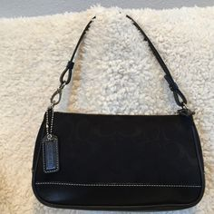 Authentic Coach Signature Top Handle This top handle is black signature fabric with smooth leather at the base. The handle can be detached on one side to turn it into a wristlet. There is a small mark on the back of the bag on the leather which you can rarely see. The style # is 06094 Coach Bags Mini Bags