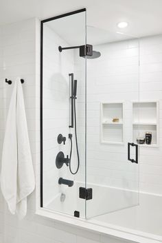 Chic black and white bathroom boasts a frameless glass shower accented with matte black hardware matching a matte black shower kit mounted to white staggered wall tiles over a tiled drop-in bathtub. White Subway Tile Bathroom, Subway Tile Showers, White Tile Bathrooms, White Tile Shower, Luxury Bathrooms, Chic Bathrooms, Minimalistic Design, Simple Bathroom, Master Bathroom