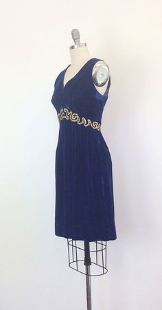 STUNNING royal blue velvet mini dress with and empire waist. The waist is decorated in gorgeous gold ribbon with patterns of large rhinestones! Flared skirt. The dress is fully lined with a metal back zipper.    c o n d i t i o n   great- no flaws to note   m e a s u r e m e n t s   fits a modern day size 6 bust - 36 inches waist - 30 inches empire waisted hips - free shoulder to waist - 14.5 inches total length - 36 inches + 3 inch hem allowance fabric - velvet     i n f o    shop…