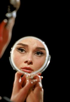 Audrey Hepburn beholds her reflection in a mirror on the set of Funny Face, portrait by Richard Avedon, 1956.