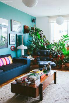 Sala de estar com parede azul e composição de quadros. Sofá e poltrona pretos com almofada colorida.
