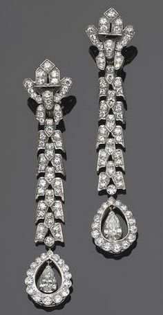 A pair of art deco diamond and platinum pendant earrings, circa 1930 each designed as a geometric line set throughout with old European-cut diamonds with pear-shaped and old European-cut diamond cluster terminals; estimated total diamond weight for the pair: 8.90 carats; length of each: 3in.