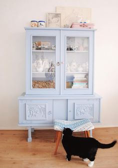 pretty blue self painted cabinet, filled with pretty porcelains.