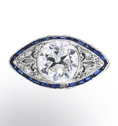 An art deco diamond and synthetic sapphire ring, circa 1920 centering an old European-cut diamond, within a navette-shaped pierced and openwork pavé-set diamond mount, enhanced by calibré-cut synthetic sapphires; center diamond weighing approximately 2.30 carats; mounted in platinum