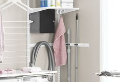 Elfa utility hooks for hanging vacuum cleaner, mops and towels in laundry room.