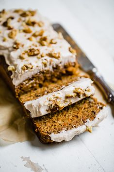 carrot cake loaf on a white board with two slices cut and a knife on the side