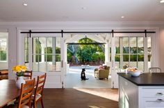 Sliding barn doors with large windows frame thebackyard - farmhouse kitchen Farmhouse Kitchen/dining room