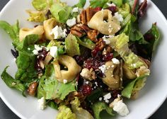 tortellini salad with cranberries, feta, and pecans  Ingredients:    Romaine lettuce and/or mixed greens – torn into bite size pieces  Tortellini – cooked per package instructions and cooled  Feta Cheese – crumbled  Pecans (or walnuts) toasted in a dry pan until just slightly browned  Dried Cranberries  Balsalmic Vinegar