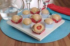 brigadeiro branco caramelado de morango em forminhas azuis e vermelhas, o primeiro docinho está mordido, mostrando o morango por dentro