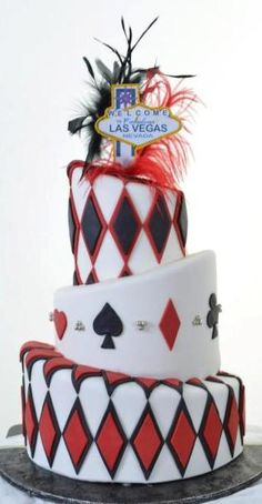 "Pastry Palace Las Vegas - Wedding Cake #1045 – Vegas Double Diamonds. Three white topsy turvy tiers of sterling white fondant accented with layers of double diamonds in black and red, faced with playing card symbols and ""Married in Fabulous Las Vegas"" sign atop."