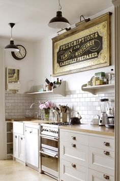 what's NOT to love in this picture?! What an amazing kitchen... / old sign / white cupboards / white tile