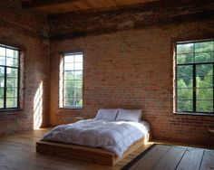 Minimalist Style Bedroom In Rustic Walling Style With Exposed Brick Featured With Low Profile Bed And Sleek Side Table