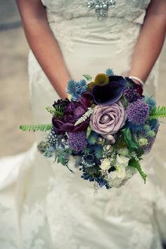 Bouquet of muted blue, purple and green flowers. Thistle, echinacea pods, calla lilies, etc