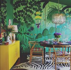 This gorgeous green room accented with bright purple and fresh yellow is designed by Molly Luetkemeyer and brings to mind easy brunches and relaxing dinners. Find your new design favorites http://www.adornomag.com/Products #interiordesign #diningroom #shapadorno #liveluxoriously #mollyluetkemeyer #green #purplepop #stpatties