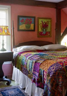 Colourful bedroom with orange pink walls and floral paintings colourful bedspread blanket colourful lampshade hand painted
