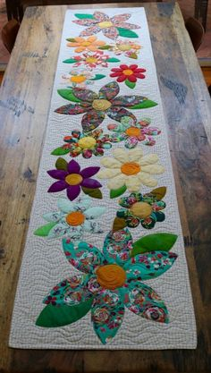 Blossoms Table Runner Paper Pattern – Free Bird Quilting Designs 2019 - - Wedding Decorations 2019 - World TrendsThe Blossoms table runner is an easy project perfect for a quick finish. The appliqué is made up of simple shapes and is laid onto the Mini Quilts, Small Quilts, Lap Quilts, Table Runner And Placemats, Quilted Table Runners, Patchwork Table Runner, Quilted Table Runner Patterns, Fall Table Runner, Quilting Projects