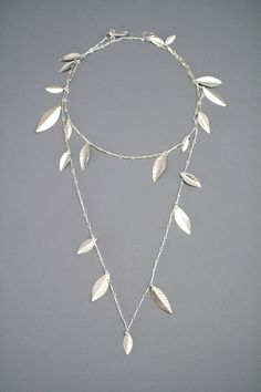 36 of bright silver chain is adorned with hand shaped sterling silver leaves. The leaves have a hammered texture and a bright shiny finish so they shimmer in the light as you move. Extra long chain allows this necklace to be worn wrapped around the neck once or twice for a doubled look. Finished with my signature handmade clasp.  Matching earrings  https://www.etsy.com/listing/126302334/extra-long-sterling-silver-triple?ref=shop_home_active_8