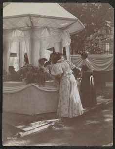 Gilded Age NYC scene in c.1896, of women at a Garden Party, to benefit Barnard College. Fashioned ladies of the era, at a beautiful elaborate tent, with flower bouquet's. Location: 37th Street and 5th Avenue. ~~ {cwl} ~~ (MCNY/Getty/Byron Image)